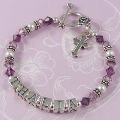 Child Name Bracelet - C02  Birthstone crystal bracelet featuring Swarovski crystals and pearls and Bali sterling silver beads. This image shows the C02 design with the Rose toggle clasp and plain cross charm – large letter blocks. Crystal colours – amethyst and light amethyst. Pearl colour – white.