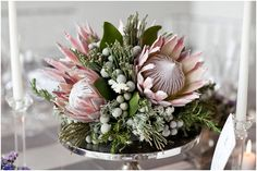 Beautiful Centerpiece Comprised Of: King Protea, Silver Brunia, Fresh Rosemary, Greenery & Foliage Flor Protea, Protea Bouquet, Protea Flower, Wedding Table Centerpieces, Wedding Flower Arrangements, Floral Centerpieces, Floral Arrangements, Wedding Decorations, Calla Lilies