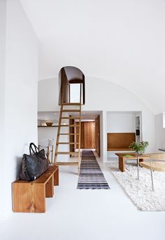bright white living space // ladder, lofted alcove, wood benches, shaggy rug & mid century chair #homedecor #interiordesign #minimal #livingroom