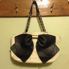 Betsey Johnson cream and black bow handbag Gorgeous, lightly used handbag in excellent condition. Fun printed lining with 3 pockets. Cream colored with a large black bow on the front. Gold chain link handles. Vegan leather. 18''x 12'' inches. Roomy. Betsey Johnson Bags Shoulder Bags