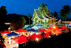 Haw Pha Bang Temple seen behind the night market at Haw Pha Bang Temple is one of Luang Prabang's most attractive monuments. by: Matthew Williams Best Places To Honeymoon, Honeymoon Destinations, Laos Destinations, William Ellis, Matthew Williams, Honeymoon Planning, Luang Prabang, Wedding Honeymoons, Day Tours