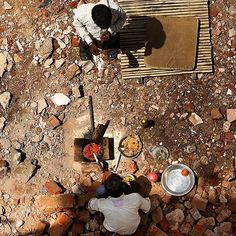 At a construction spot, a labourer cooks a simple lunch using only onions and tomatoes with roti while his friend eagerly waits for the food.  Picture credits: @jasjeetplaha