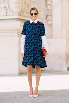 Blogger Helena Bordon wears a printed shift dress with a white collared button down underneath.