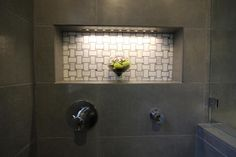 This master bathroom has a luxurious gray tile shower with a niche boasting white basket weave tile. The niche is illuminated by soft LED lighting.