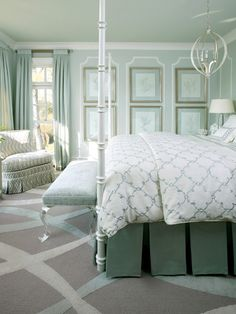 Chic bedroom with mint walls paint color, art gallery, Currey & Co. Luna Chandelier, white poster bed, white & blue quatrefoil pattern bedding, green pleated bed skirt, acrylic bench and mint curtains.