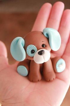 This listing is for one hand sculpted polymer clay puppy cake topper. The puppy is in the sitting position and is approximately 2.5 tall. The body of the puppy is caramel brown with either baby blue or pink accents. Comes with a bone (1.5 long) complete with tiny color-coordinated heart.