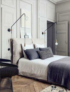 sol en vieux parquet bois clair tapis beige couverture de lit grise linge de lit balnc
