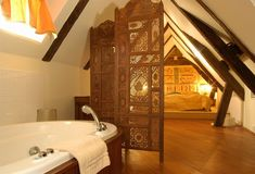 Oh, wow...what a sexy attic bathroom.  Exotic dividers and a tub with a wooden surround.... :O wow.