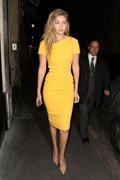 Out to dinner in Paris wearing a yellow Victoria Beckham sheath dress and nude pumps.    - HarpersBAZAAR.com