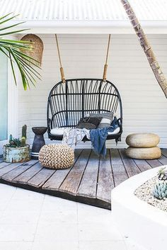 Create tropical vibes with a porch swing surrounded by pieces in rattan and natural wood.