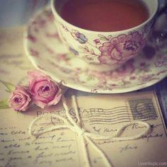 Fotos vintage, rosas, chavena de chá e postais