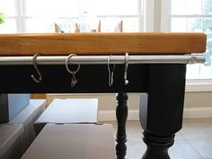 conduit fastened to table with S hooks for handy storage of cutting tools, rulers, etc.