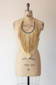 Vintage 1970s tan soft leather halter crop top with tie neck and back. This amazing little bohemian top has pewter trim details and a fringed bust.