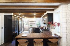 Love the wood beams, butcher block counters and how the subway tile covers an entire wall. Need this.
