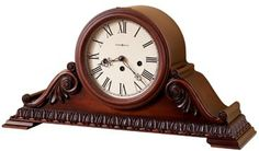 """The Howard Miller Newley 630-198 Keywound Mantel Clock is a classic tambour clock. The base features a decorative molding that wraps around three sides of the clock. The bookmatched leaf and rosette patterns flank the bezel and dial. The dial features Roman numerals, black spade hands, convex glass and a hinged bezel. Finished in Americana Cherry it features German Key-wound, Westminster chime movement with chime silence option and durable bronze bushings. Size H. 11-1/2"""" W. 22"""" D. 6-3/4"""""""