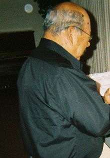 Michelle D. took this photo at her father's wake. Her uncle has an orb behind him where he is standing.