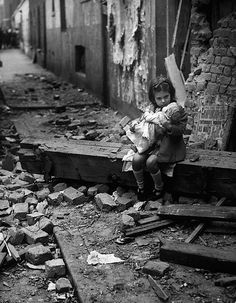 1940's. The little girl is sitting outside of her London home, which has been bombed out during the Blitz., girl with doll, solitude, desperate times, forfald, rubbles, ruins, history, photo, black and white