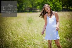 Senior Portraits Austin Texas: http://seniorportraitsaustin.com. A brunette teen high school senior female poses for her senior portraits photo session wearing a white dress while smiling and standing in a field of tall grass outdoors with the sun shining down on her.