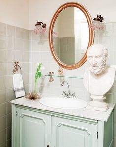 A marble bust adds a cheeky element to this powder room