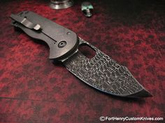 Jeremy Horton – Damascus Bowie.  The frame is Lightning Strike Carbon Fiber, the blade is Chad Nichols Stainless Damascus.  The thick Framelock Ti side have been aggressively Stonewashed for maximum protection.  The blade opens with an extremely smooth motion and the Lock engages Early and Securely.     It will ride comfortably in the pocket using the discreet Deep Carry clip and due to its Titanium and Carbon Fiber construction it is very light for its size.