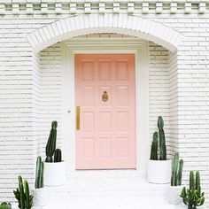 Cute palm Springs inspired exterior: white brick, pink door, tons of cacti!