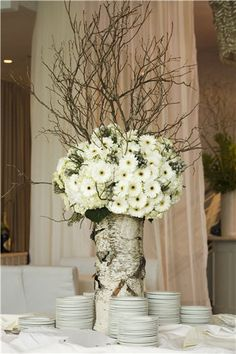 birch vases, white flowers, curly willow or other branches for centerpieces ~ http://blog.bigappleflorist.com/january-wedding-flowers/