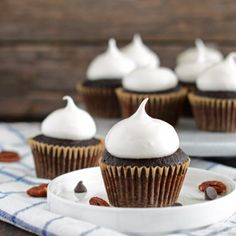 Homemade dark chocolate cupcakes baked with toasted pecans and chocolate chips, then topped with homemade marshmallow frosting.