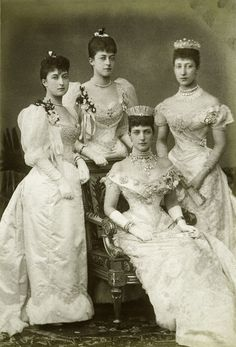 Photograph of the Princess of Wales, later Queen Alexandra and her three daughters. From left to right: Princes Maud, standing; Princess Victoria, standing behind her mother's chair; the Princess of Wales, seated, fan on her lap, wearing ornate necklace, tiara; Princess Louise, Duchess of Fife, standing. They are dressed in evening gowns