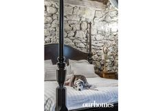 """The stone walls in the basement are original. All walls were painted with organic milk paint in white. The owner's Greyhound, Lee, relaxes in the master bedroom.   See more of this home in """"Designer Creates a Divine Home in Former Church"""" from OUR HOMES Barrie Holiday/Winter 2016/2017 http://www.ourhomes.ca/articles/build/article/designer-creates-a-divine-home-in-former-church"""