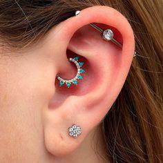 Chica con un piercing en la oreja en color turquesa