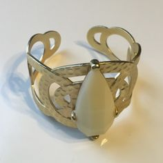 Gold cuff bracelet with cream stone This adorable statement cuff would definitely dress up a little black dress, perfect to complete your work outfit, etc. The stone is plastic and the cuff is metal. Only a little bit of imperfections on the inside, which you won't see when on. ALL JEWELRY IS BUY ONE GET INE FREE!! Jewelry Bracelets