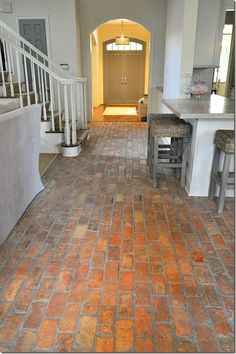 Brick floor in the kitchen. Warm and inviting. (Put a drain in the floor and all you have to do is spray it down!)