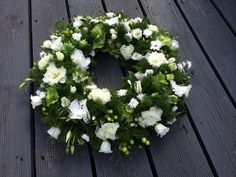 White ivory and green funeral wreath. Compact design with small flowers for delicate and intricate detail