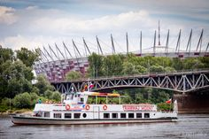 Wars water tram (tramwaj wodny) with the National Stadium (Stadion Narodowy) and the Srednicowy railway bridge over the Vistula (Wisla) river, Warsaw, Poland