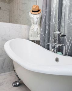 A fun, sequined dress mannequin topped with a hat is the perfect accessory for this curvy, footed bathtub in the master bathroom.