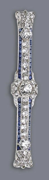 An art deco diamond and sapphire brooch, circa 1925 centering an old European-cut diamond, accented by two single lines of calibré-cut sapphires, within an old European and single-cut diamond surround, completed by openwork scrolling terminals; central diamond weighing approximately: 1.00 carat; remaining diamond weight approximately: 4.50 carats; mounted in platinum; length: 3 3/16in.