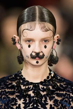 "Ricardo Tisci called his Fall/Winter 2015 Givenchy girl a ""Chola Victorian."" The models pulled this vibe off with face jewels coming out of every orifice and even secured to skin in unlikely places."