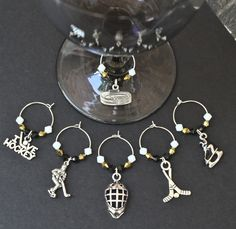 PENGUINS HOCKEY WINE CHARMS-This is a set of 6 hockey theme charms.  Included in this set are one stadium, one hockey player, one goalie mask, one enamel skate, one set of hockey sticks, and one I LOVE HOCKEY charm.  Crystal beads in colors of black, gold, and white were used, along with silver metal accent beads.  This set was made for PITTSBURGH PENGUINS fans. I can make just about any team's colors. Just convo me with your request.