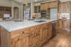 High-end finishes including knotty alder cabinets, granite countertops and tile backsplash in this Pahlisch Homes kitchen.