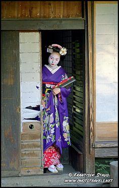 Photograph of Maiko girl (Geisha apprentice) leaving an old Japanese Teahouse, Kyoto, Japan photos