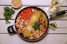 INGRÉDIENTS (environ 4 portions) 350 gr (12 oz) de nouilles linguine sèches 2 gousses d'ail hachées 1 c. à soupe de gingembre frais haché 1 poivron rouge coupé en julienne 1 carotte coupée en julienne 4 oignons verts hachés 500 gr de crevettes décortiquées (fraîches ou décongelées) 2 c. à soupe de sauce nuoc-mâm (sauce de poisson) 1 litre (4 tasses) de bouillon de légumes 1 c. à soupe d'huile de sésame Une bonne poignée de coriandre fraîche hachée grossièrement Arachides hachées 2 citrons…