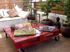 Awesome wood pallet coffee table on wheels...painted a beautiful red and topped with glass.
