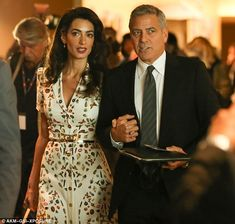 Amal Clooney with her husband, George.  Amal is wearing a Alexander McQueen dress.  Sort of reminds me of the Duchess of Cambridge's Alexander McQueen dress she wore at Wimbledon this year.