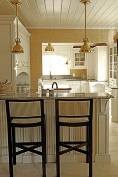 Lovely fresh yellow and white kitchen with tongue and groove ceilings and gorgeous pendant lights.