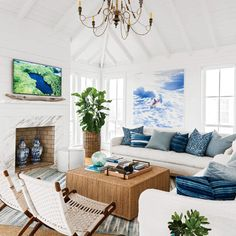 "In this Sullivan's Island, South Carolina, living room, designer Jenny Keenan layered old and new for a look that's both ""livable and timeless."" Crisp white shiplap walls are a clean backdrop for the room's mix of collected items: a vintage dhurrie atop a sea grass rug, a pair of Hans Wegner chairs, and a vibrant surf painting by Isca Greenfield-Sanders."