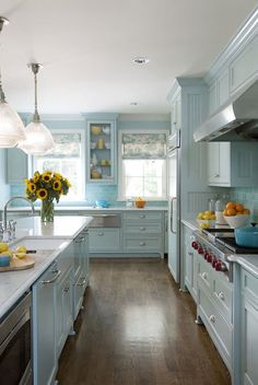 Fantastic blue kitchen features blue cabinets painted Sherwin Williams Tidewater accented with blue beadboard trim topped with white marble and blue subway tiled backsplash framing a stainless steel hood over integrated Wolf Range with pot and pan drawers below.