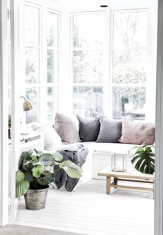 Lovely all white living room with hints of pastel colours and the obligatory green plants.