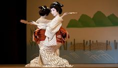 Two geisha perform for the Miyako Odori, an annual festival where geisha can showcase what they have learned