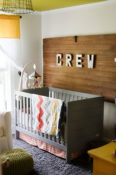 Bright Nursery, green, yellow curtains, wooden door, silver letters, name, grey crib, fuzzy rug