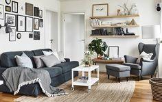 Aufnahme eines Wohnzimmers in neutralen Farben, darin sind ein Sofa, Sessel und Regale zu sehen.